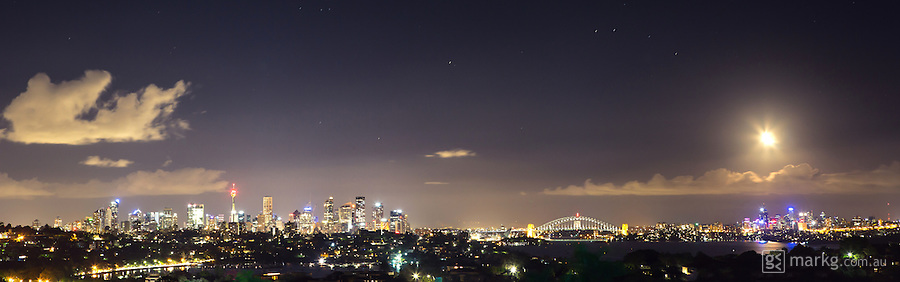 Panographic view of the Sydney skyline at night as the moon sets to the west of the city.