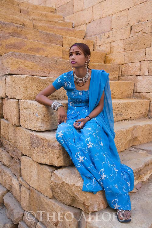 Rajasthani girl sitting on steps in Jaisalmer Fort, Jaisalmer, Rajasthan, India --- Model Released