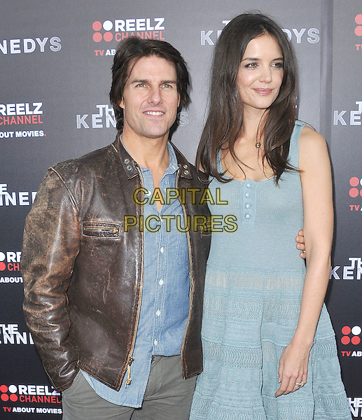 "TOM CRUISE & KATIE HOLMES.attending the World Premiere of ""The Kennedys"" at The Academy of Motion Pictures Arts And Sciences, Samuel Goldwyn Theater in Beverly Hills, California, USA, March 28th, 2011..half length husband wife married couple brown leather jacket green blue dress buttons vest sleeveless shirt  S initial necklace gold letter  hand in pocket      tall short                                                                    .CAP/RKE/DVS.©DVS/RockinExposures/Capital Pictures."