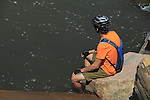 Male biker sitting and resting along Boulder Creek, Boulder, Colorado. .  John offers private photo tours in Denver, Boulder and throughout Colorado. Year-round Colorado photo tours.