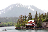 USA, Alaska, Homer, a home and fishing boat in Halibut Cove in the evening time