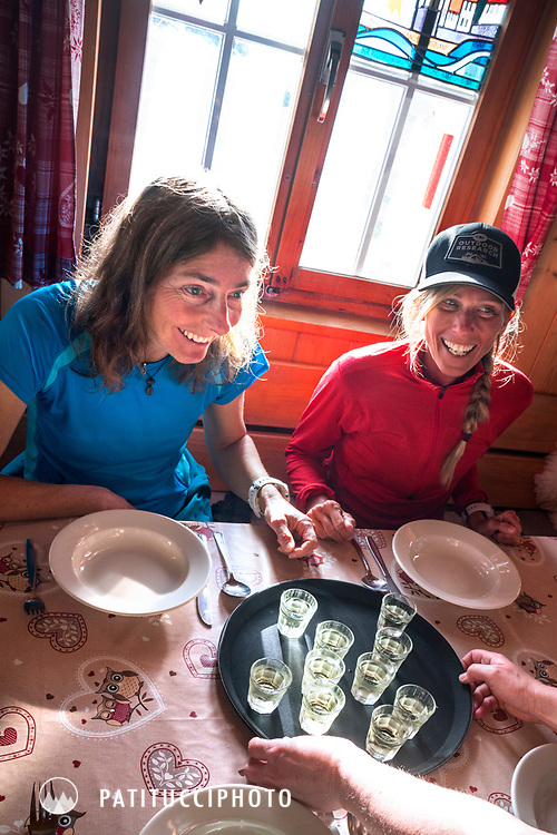 Two women being served drinks at the Tierbergli Hut while on a ski tour of the Berner Haute Route, Switzerland