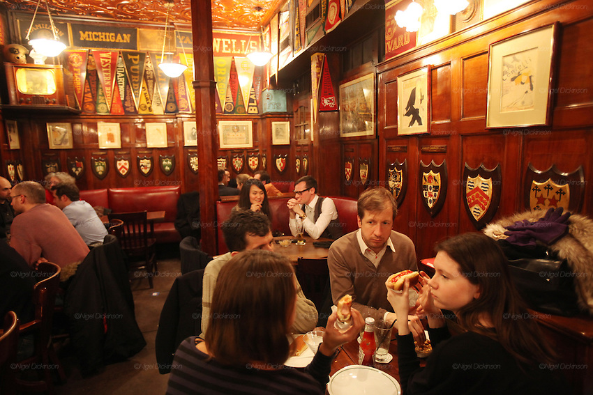 Harry's New York Bar in central Paris near the Opera is renowned for its cocktails, american style hot dogs, piano bar and private and friendly atmosphere. The hot dogs taste as if they were from a New York street seller. There is a huge range of classic and modern coctails, and a variety of outstanding whiskies, malts and Rye from across the world. This friendly ambience comes at a price, cocktails cost around EUR15///Clientele eating the famous New York style hot dogs