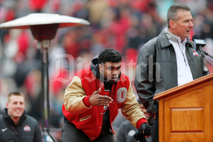 Running back Ezekiel Elliott sneaks up on coach Urban Meyer as he's being introduced during the Ohio State football National Championship celebration at Ohio Stadium on Saturday, January 24, 2015. (Columbus Dispatch photo by Jonathan Quilter)