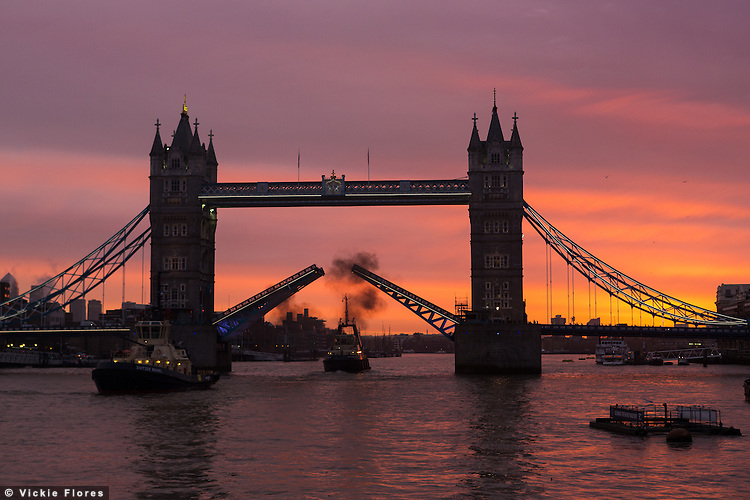 A pink and orange sunrise behind a raised Tower Bridge, just before sunrise as Svitzer Brunel and Svitzer Mercia leave after assisting the arrival of German frigate FGS Schleswig-Holstein, F216 on Friday 24 January  2014..  Unsettled weather and rain are forecast from today, following a period of unseasonably mild weather this January.