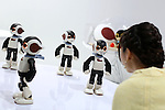 """A woman speaks to communication robots called """"Robi"""" during a press preview for """"Robi cafe"""" where visitors can interact with the robots while enjoying meals and drinks in Tokyo, Thursday, January 15, 2015. The robot can be built by assembling parts sent along with a weekly magazine by Deagostini. The cafe will open from January 16 until February 8. (Photo by Yuriko Nakao/AFLO)"""