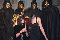 Girls wearing black masks holding a lit candle.