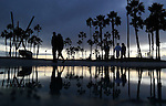 People walk past a puddle formed by rain in Venice Beach.