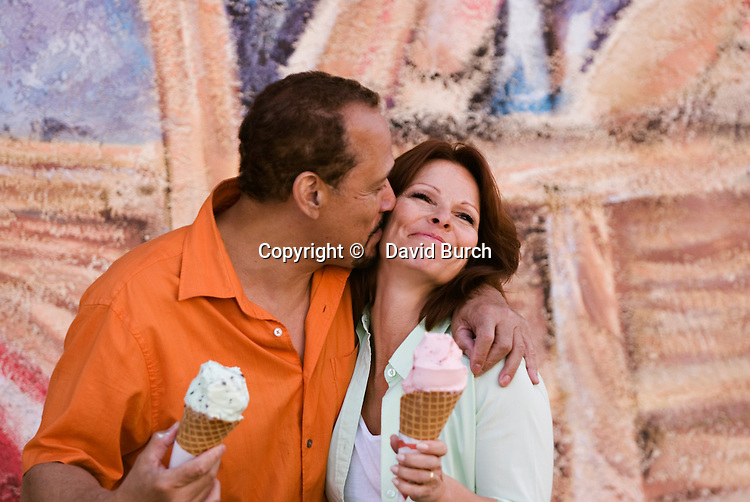 Mature man kissing wife while holding ice cream cone