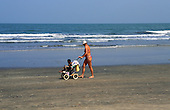 The Gambia. White-skinned tourist pushing a black-skinned child in a buggy along a beach.