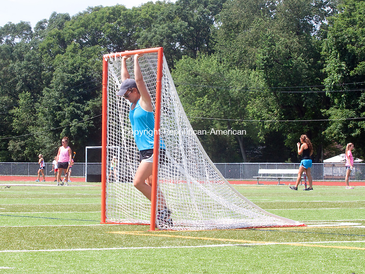 CHESHIRE- JULY 10 2014 070914DA13- The head coach of the Cheshire Field Hockey Team Eileen Gallagher moves a lacrosse net off the field in preparation of practice during day two of its camp at Cheshire High School on Wedesday.<br /> Darlene Douty Republican American