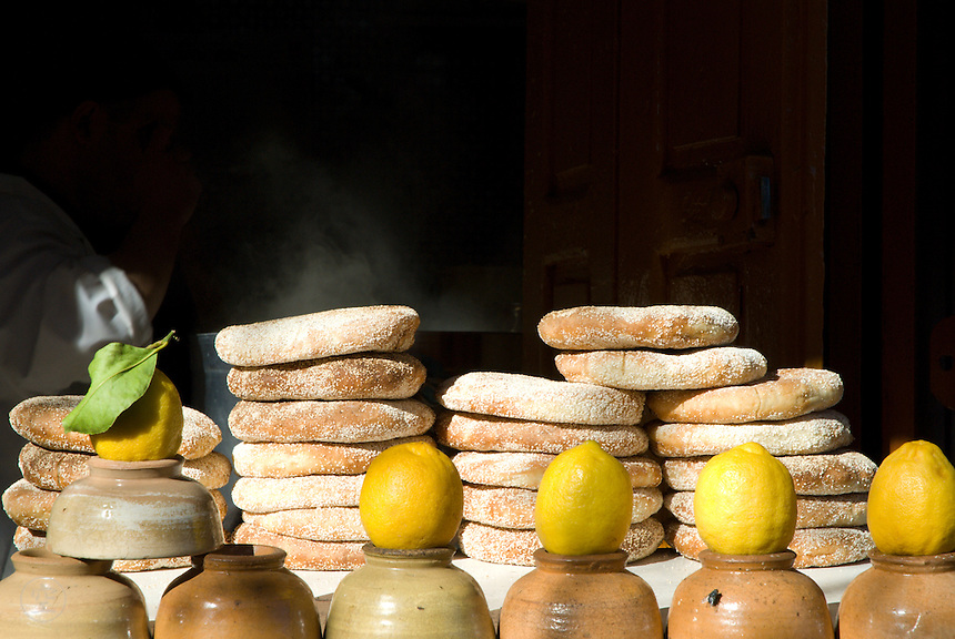 Lemons and flatbreads catch the sunlight at the entrance to a harira soup shop in Fez, Morocco.