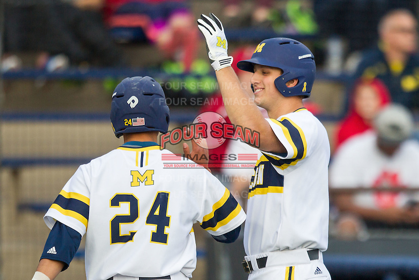 Michigan Wolverines outfielder Carmen Benedetti (43) greets second baseman Hector Gutierrez (24) after he scored against the Eastern Michigan Hurons on May 3, 2016 at Ray Fisher Stadium in Ann Arbor, Michigan. Michigan defeated Eastern Michigan 12-4. (Andrew Woolley/Four Seam Images)