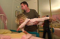 7:54 PM: Joe Twarowski whirls his daughter Lena, 3,  into bed in Pleasanton, Calif., Thursday Oct. 21, 2004. Twarowski, works for a Silicon Valley company but choses to live in Pleasanton. (Alan Greth)