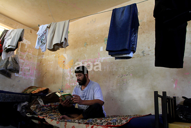 A Palestinian prisoner reads the holy Koran in a Hamas-run jail on the fourteenth day during the holy month of Ramadan in Gaza City on Aug. 14, 2011. Muslims around the world are observing the holy fasting month of Ramadan in which they refrain from eating, drinking, sex and smoking from dawn to dusk. Photo by Ashraf Amra