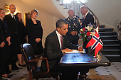 United States President Barack Obama signs the book of condolence at the residence of the Norwegian ambassador.  In the background,  Norwegian Embassy staff, Charge d' Affairs, Barit Enge, Military AttachÈ   Col Roy Abelson, Vice President Joseph Biden Jr..Credit: Dennis Brack / Pool via CNP