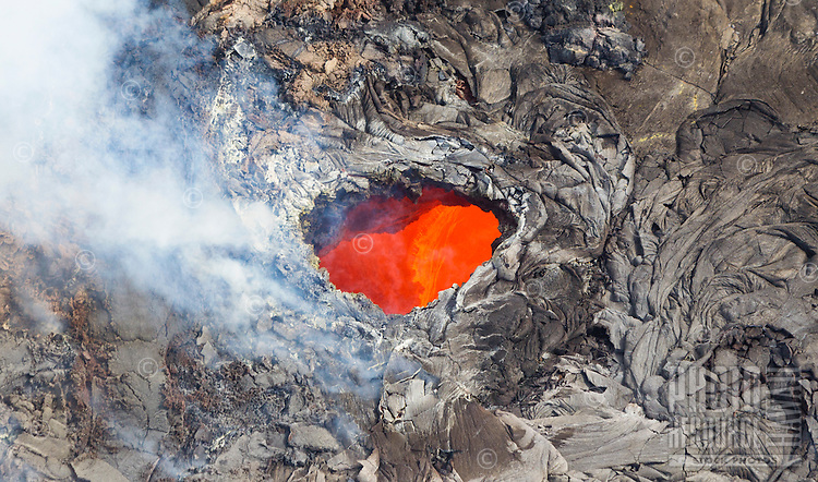 An opening in a lava tube offers a view of molten lava, Pu'u O'o Vent, Hawai'i Volcanoes National Park, Big Island.