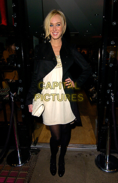 KIMBERLY STEWART.Mascaro - store launch party, Mascaro, Marylebone High Street, London, England..November 19th, 2007.full length kimberley white cream dress black tights mary janes shoes heels clutch bag purse coat jacket hand on hip .CAP/CAN.©Can Nguyen/Capital Pictures
