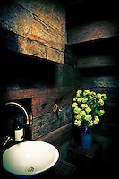 An arrangement of green flowers in a blue vase stands on a box in the corner of a bathroom with wood cladded walls. A chrome tap stands over a round wash basin.