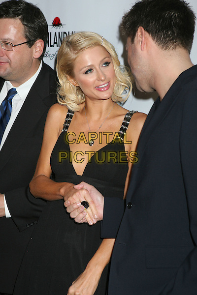 PARIS HILTON.In Touch Weekly's Summer Stars Party 2008 held at Social Hollywood, Hollywood, California, USA,  .22 May 2008..half length shaking hands curly hair  hair clip black dress .CAP/ADM/MJ.©Michael Jade/Admedia/Capital Pictures