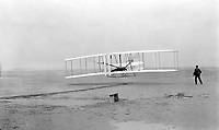 1903 Dec. 17- One of the first flights, 120 feet in 12 seconds, 10:35 a.m.; Kitty Hawk, North Carolina.<br /> Orville Wright at the controls of the machine, lying prone on the lower wing with hips in the cradle which operated the wing-warping mechanism. Wilbur Wright running alongside to balance the machine, has just released his hold on the forward upright of the right wing. The starting rail, the wing-rest, a coil box, and other items needed for flight preparation are visible behind the machine.<br /> <br /> <br /> FranÁais : Líun des premier vols habitÈs de líhistoire dans un aÈronef plus lourd que líair (40 mËtres en 12 secondes), par les frËres Wright le 17 dÈcembre 1903 ‡ 10h35 sur la plage de Kitty Hawk en Caroline du Nord.<br /> Orville est aux commandes, allongÈ sur le ventre sur líaile basse et les hanches dans la nacelle qui servait ‡ contrÙler le mouvement des ailes ; Wilbur court le long de líappareil et vient de lacher líaile droite. Le rail de lancement, des Ètais et díautres Èquipements nÈcessaires pour la prÈparation du vol sont visibles.
