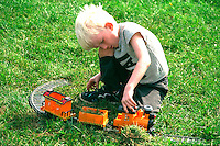 Boy age 6 playing conductor with toy train at Como Park.  St Paul  Minnesota USA
