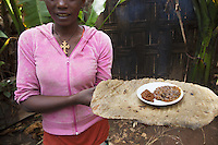 Ethiopia. Southern Nations, Nationalities, and Peoples' Region. Omo Valley. Hayzo Village. High altitude: 2800 meters. Dorze tribe. A young woman with ensete or false banana as a cooked preparation on fire of food dough and bread, called Kocho, holds also a plate with spicy peppers and wild honey. The Dorze are a small ethnic group inhabiting the Gamo Gofa Zone who speak the Dorze language, an Omotic tongue. The Dorze are predominantly agriculturalists living in permanent villages. Ensete ventricosum, commonly known as the Ethiopian banana, Abyssinian banana, false banana, or ensete, is an herbaceous species of flowering plant in the genus Ensete of the banana family Musaceae. The Dorze numbered 40'000 reside in villages near the cities of Chencha and Arba Minch. Southern Nations, Nationalities, and Peoples' Region (often abbreviated as SNNPR) is one of the nine ethnic divisions of Ethiopia. 6.11.15 © 2015 Didier Ruef