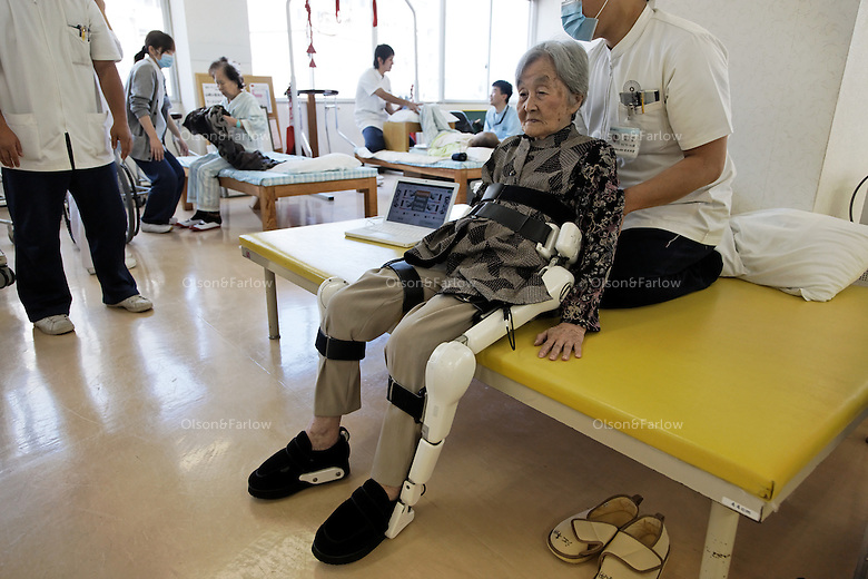 "Robot HAL at Akanekai Showa HOSPITAL.http://www.akanekai-showa.com.Rehabilitation Section at the Showa hospital uses these HAL legs to help elderly that have a hard time walking.  These are ACTUALLY in use on a daily basis... outpatients (usually) come in twice a week and have a number of electrodes placed in key areas on their legs and lower torso.  These electrodes monitor minor changes in muscle activity and transfer that information to the robotic joints.  Woman being put into the legs is:.EMOTO (Last Name), Chiyoko (89) : She had a fracture of right and left thighbone.The main woman therapist working with her is TSURUGA (Last Name), Mai (P.T.).All of these robotics folks developing robots for elderly talk about studies showing that more and more elderly are isolated and have no one to relate to... In 2009 it was 19 percent of the elderly population of Japan.  They have a word for it:  ""Kodokushi"" or ""lonely death.""."