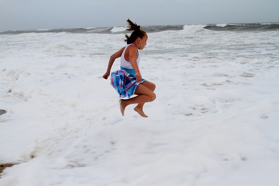 Emma White, 8, leaps into the rough surf of the Atlantic Ocean in Buxton, NC, as the first rain bands of Hurricane Irene began to pass over the Outer Banks on Friday, Aug. 26, 2011.  Photo by Ted Richardson
