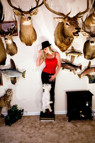 Model Megan Holmberg posing with mounted animal heads at her father's apartment in Lakewood, Colo.  The Holmbergs are avid hunters and gun enthusiasts.