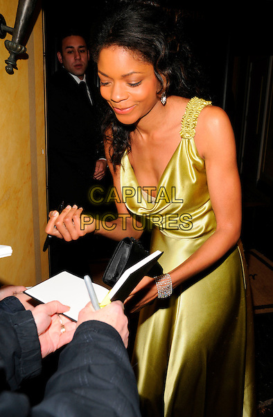 NAOMIE HARRIS.The Chain of Hope Annual Ball, Dorchester Hotel, London, England..January 4th, 2008.half 3/4 length green gold yellow satin silk dress bending leaning signing autographs .CAP/CAN.©Can Nguyen/Capital Pictures