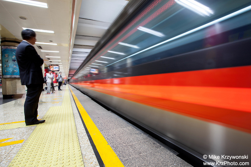 Passengers wating to ride a speeding subway in Beijing, China