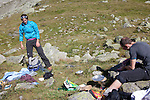 Climbers organize their gear during a lunch break on the Plan D'Aiguille, midway up the mountain from Chamonix to the Aiguille du Midi, Chamonix-Mont-Blanc, France