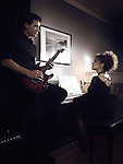 Young couple playing music in romantic dimly lit indoor settings. Woman is playing piano and a man playing guitar.