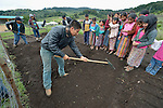 School children prepare garden plots and plant vegetables in San Jose la Frontera, a small Mam-speaking Maya village in Comitancillo, Guatemala. The program is jointly sponsored by the community's school and the Maya Mam Association for Investigation and Development (AMMID). Demonstrating how to rake is Estuardo Aguilon, an agricultural specialist with AMMID.