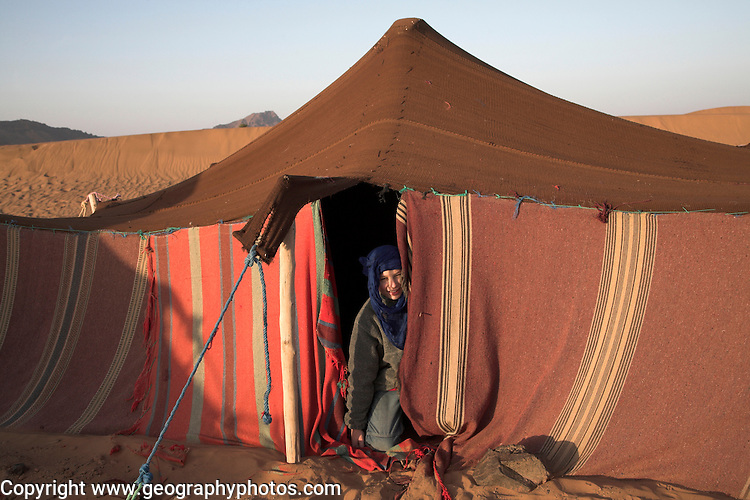 Model Released Young tourist boy dressed with blue nomad head scarf kneels at the entrance to a Berber tent, Sahara desert, near Zagora, Morocco, north Africa