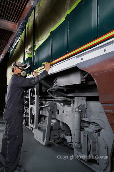 Painter prepping train engine at repair factory