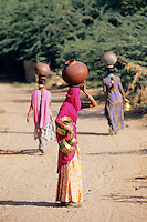 India, Rajasthan, near Udaipur: Local women carrying baskets on heads | Indien, Rajasthan, bei Udaipur: junge Frauen tragen Wasserkruege auf den Kopf