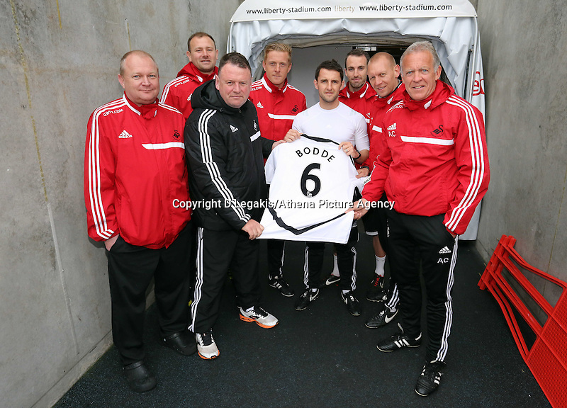 Wednesday, 23 April 2014<br /> Pictured: Coaching staff including head coach Garry Monk, first team coach Alan Curtis and physio Richie Buchanan hold a no 6 shirt for former player Ferrie Bodde who is in an induced coma suffering from pneumonia.<br /> Re: Swansea City FC are holding an open training session for their supporters at the Liberty Stadium, south Wales,