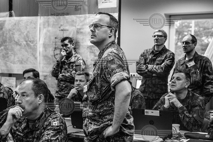 Captain Hardie, from the Canadian Army, with other officers in the situation room during NATO Iron Sword joint exercises.