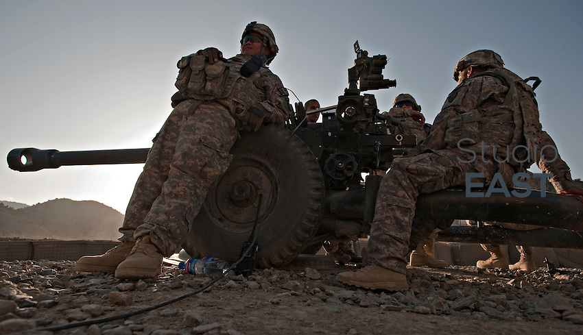 American soldiers of Bravo Battery, 2/377 Parachute Field Artillery Regiment, sit by their 105mm artillery field gun while they wait for clearance before a fire mission in support of a nearby American patrol base in Paktia Province, Afghanistan. 3 September 2009. More than 60,000 U.S. troops are now in the country to combat rising insurgent violence. The U.S.-led NATO coalition in Afghanistan now has lost more troops this year than in all of 2008, and August has since become the deadliest month for the Americans since U.S. operations began nearly eight years ago. Photo by Simon Lim/Pictobank