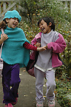 Two girls with their school bags, in playful walk, laughing, holding hands.  One wears matching pink knitted hat and vest; her friend, with Indian features, wears loose sweatshirt.