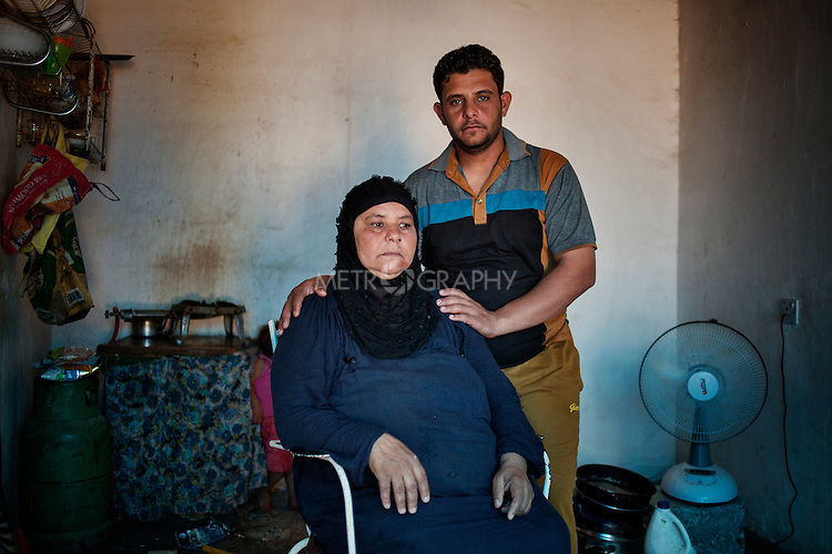 28/08/15. Shaqlawa, Iraq. -- A portrait of Fawziya and her youngest son (24) Mohamed, displaced from Falluja. Fawziya does not remember if she is 45 or 46. She has been living in Shaqlawa with her two sons and their families for the past 7 months. They left Falluja after that one day a bomb hit and destroyed their house killing Fawziya's daughter. In Shaqlawa they are renting two small concrete shacks, for which they pay 400 usd.