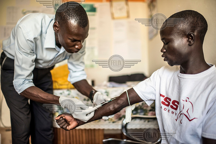 A man who visited the RHU (Reproductive Health Uganda) clinic with his partner to have STI tests gives a blood sample in the lab.