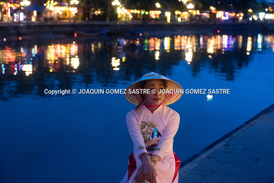 A young woman poses at the mouth of the Thu Bon River in Hoi An (Vietnam) a small town on the coast of the South China Sea<br /> HOIAN-VIETNAM
