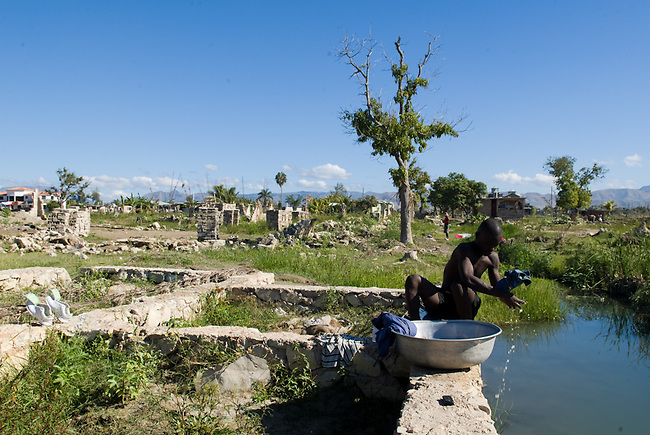 A man close to Downtown Gonaives washing his clothes in a small river. The houses in the sourrounding neigbourhood were totaly destroyed by hurrican Ike and the followig flood in September 2008.