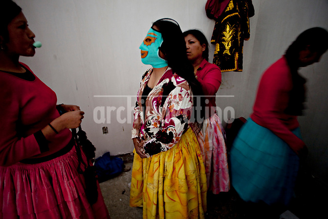 """.Aymara women known as """"Cholitas"""" getting ready to wrestler on a Sunday afternoon..Just 25 years ago it was a small group of houses around La Paz  airport, at an altitude of 12,000 feet. Now El Alto city  has  nearly one million people, surpassing even the capital of Bolivia, and it is the city of Latin America that grew faster ...It is also a paradigmatic city of the tubles and traumas of the country. There got refugee thousands of miners that lost  their jobs in 90 ¥s after the privatization and closure of many mines. The peasants expelled by the lack of land or low prices for their production. Also many who did not want to live in regions where coca  growers and the Army  faced with violence...In short, anyone who did not have anything at all and was looking for a place to survive ended up in El Alto...Today is an amazing city. Not only for its size. Also by showing how its inhabitants,the poorest of the poor in one of the poorest countries in Latin America, managed to get into society, to get some economic development, to replace their firs  cardboard houses with  new ones made with bricks ,  to trace its streets,  to raise their clubs, churches and schools for their children."""