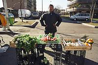Milano, mercato rionale al quartiere Bruzzano, periferia nord. Immigrato filippino laureato in ingegneria meccanica vende verdura --- Milan, local market at Bruzzano district, north periphery. Immigrant from Philippine with a degree in automotive engineering selling vegetables
