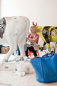 "August 9, 2012. Durham, NC.. Paula MacLeod works on ""Lady Carolina Blooo"" who has had 125 lbs. of tile added to her 125 lbs. body..  Artists from all over the state have been working at Golden Belt decorating their assigned cows for the Parade of Cows, to be held this month. After the cows are displayed around the Triangle, they will be auctioned off to benefit the NC Children's Hospital.."