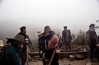 Local minority workers work on a construction project on a dirt road connecting rural villages in Yuanyang County, Yunnan Province, China. Roads in the area are being improved to increase tourism to the region's rice terraces and improve travel between the many villages in the mountainous region.